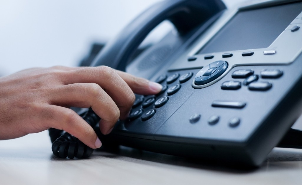 Hand dialing a button on an office phone to make a business call.