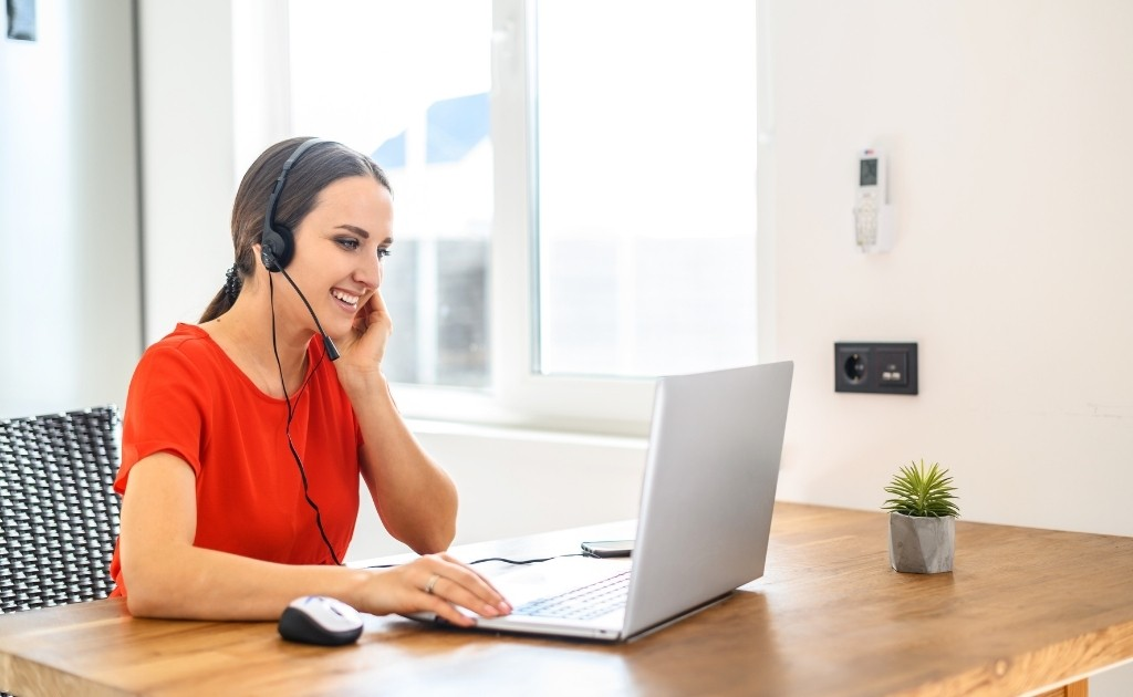 A smiling woman, working at a desk wearing a headset to answer calls as part of her call handling job.
