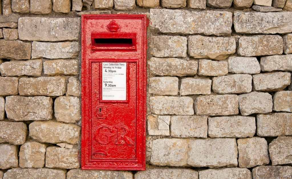 Beige brick wall, with a red UK post box. Having a UK address helps to create a business presence.