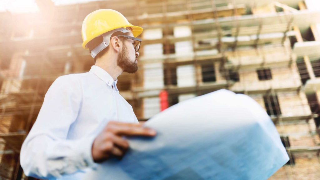 Man wearing a hardhat, holding a building plan in front of a building with scaffolding