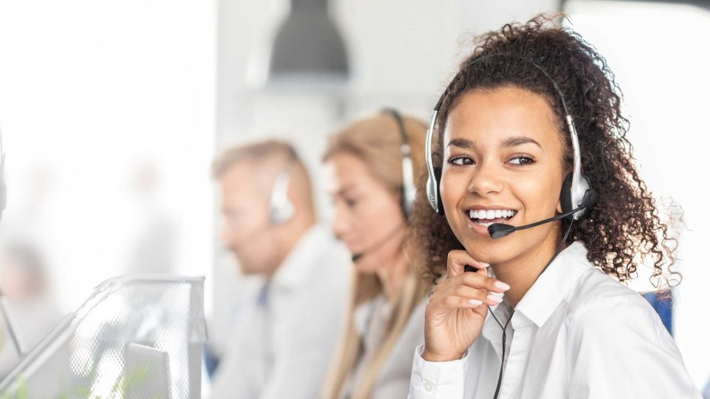 Smiling UK virtual receptionist wearing a headset answering calls