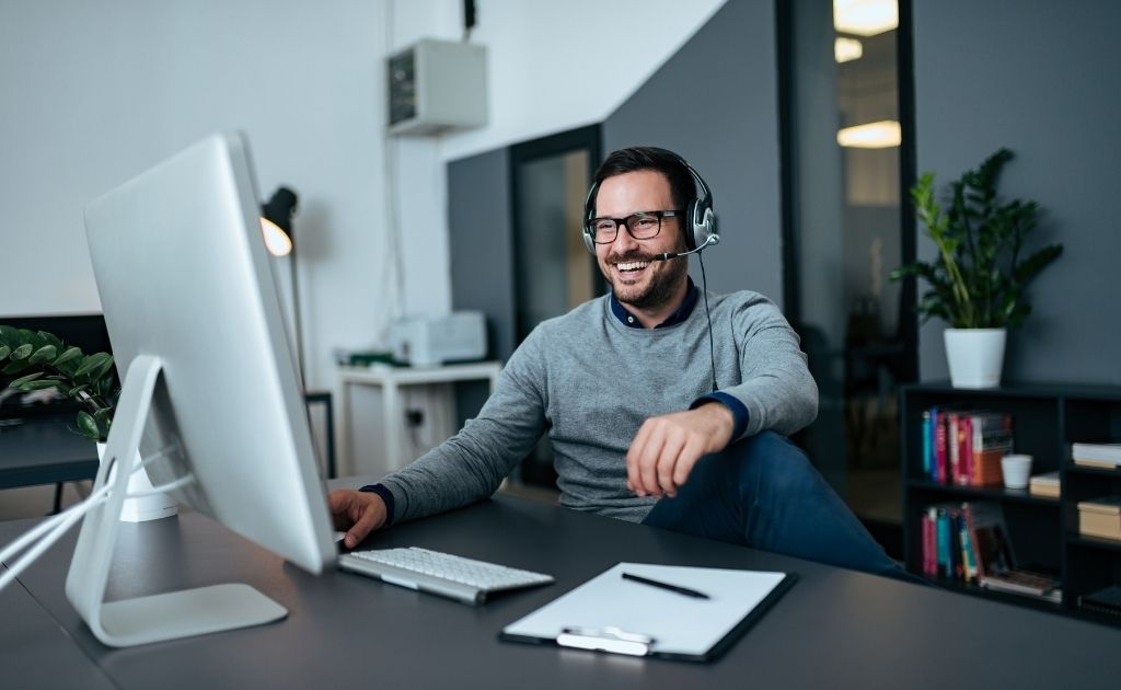 Man with headset responding as small business live answering agent