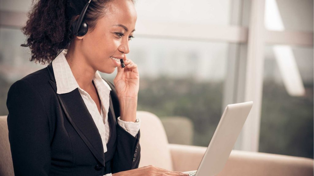 Smiling woman working as a UK virtual receptionist, chatting to a customer on a headset, sitting in front of a laptop.