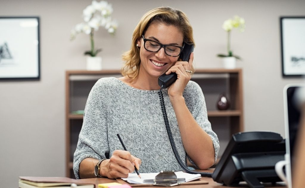 Smiling woman wearing glasses, answering a telephone call and taking notes with a pencil.