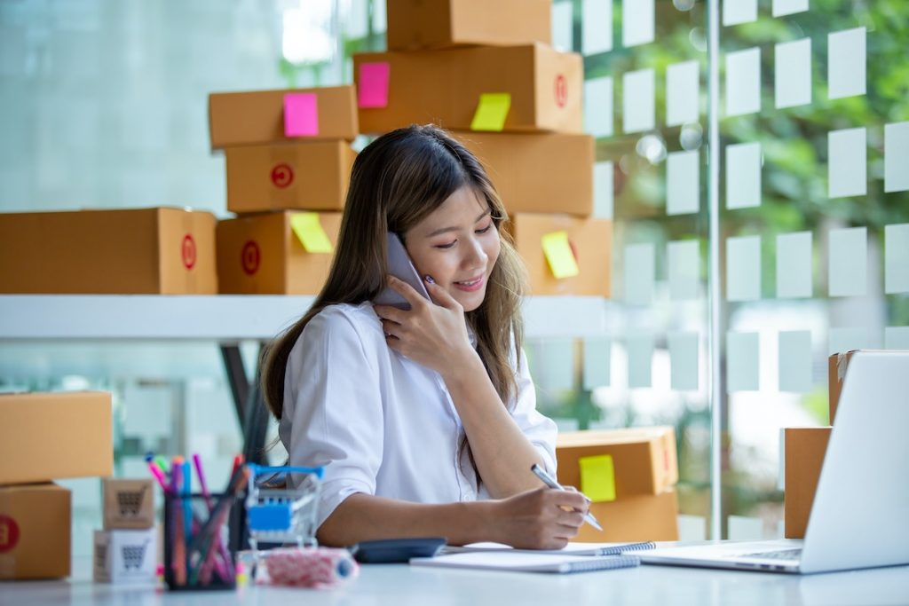 Smiling receptionist on call to customer using Appointment Scheduling Service