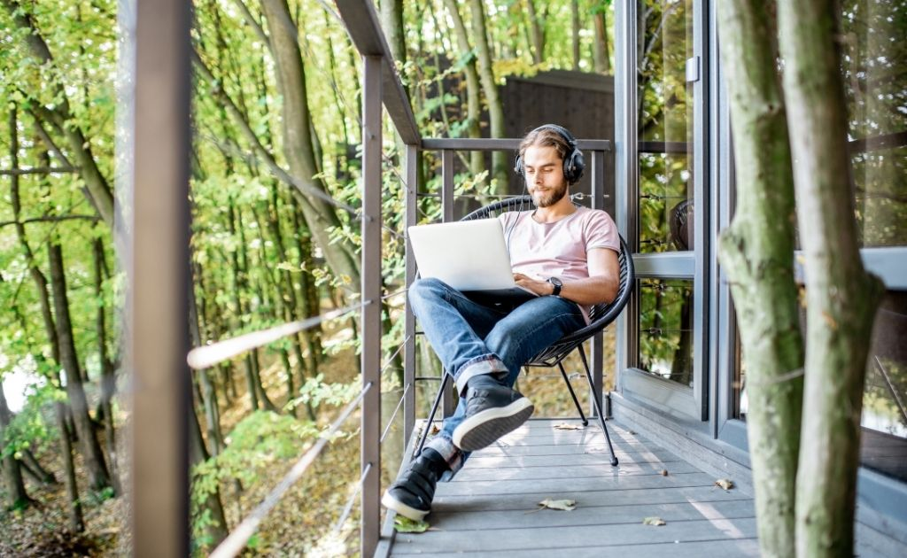 Man with headphones and a laptop, engaging in remote work while sitting outside.