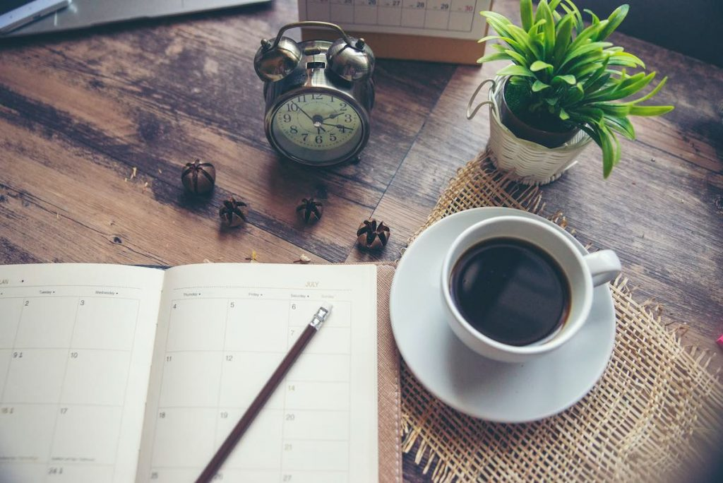 Paper diary and coffee on table