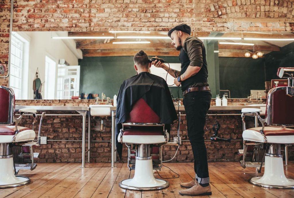 Man cutting customers hair in barbers booked in using appointment scheduling