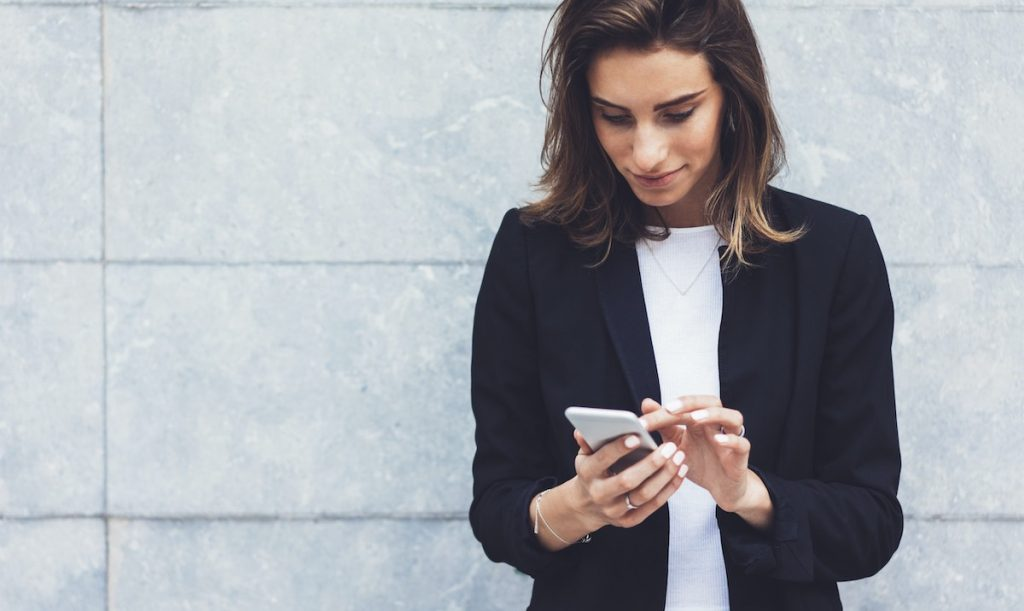 Woman smiling looking at smartphone for learning time