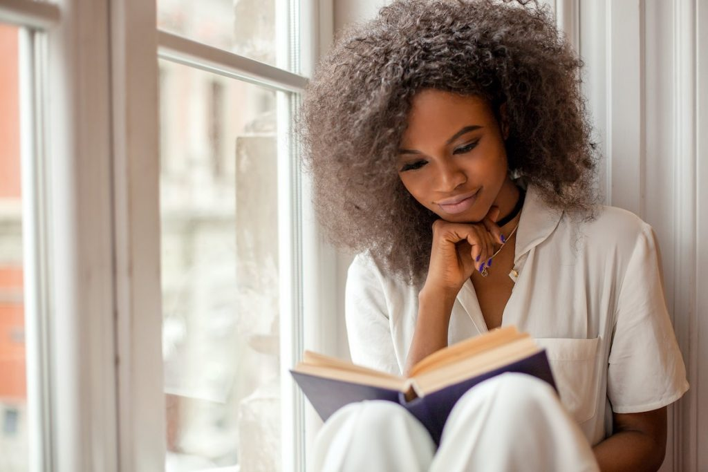 Woman smiling reading book by window as part of learning time