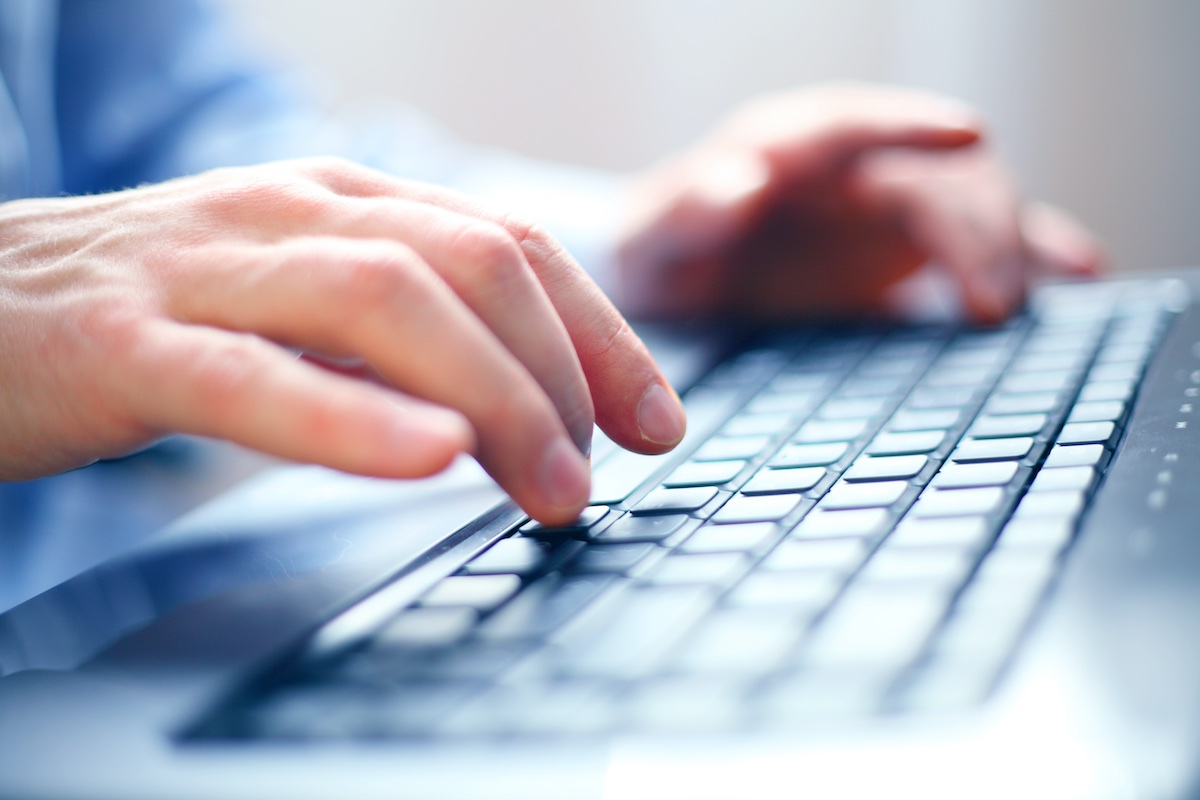 Hands typing on laptop replying to customer via omnichannel support team