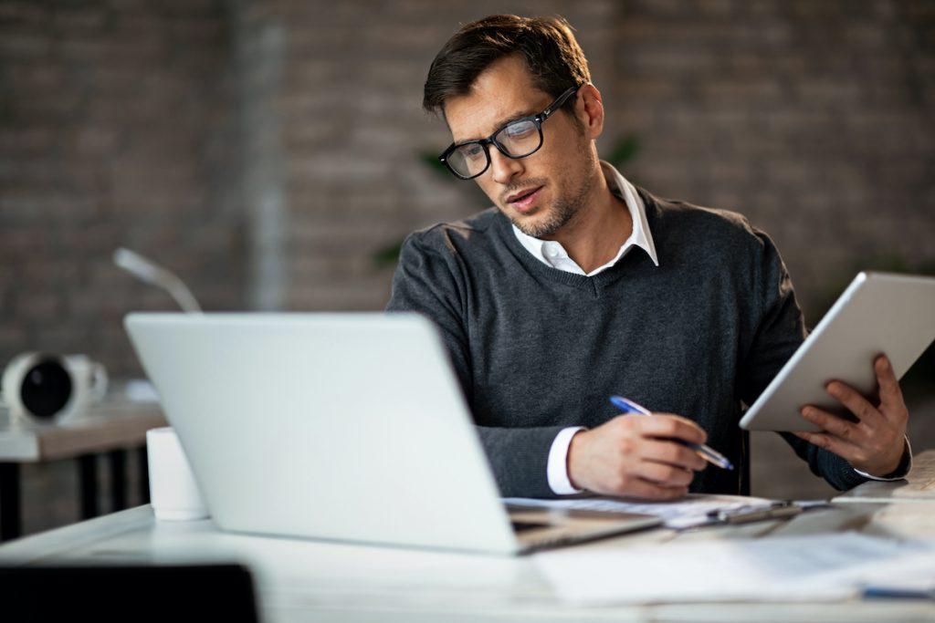 Man taking notes during video meeting on laptop