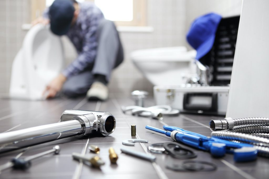 Plumber working on job from job picked up by contractor answering service