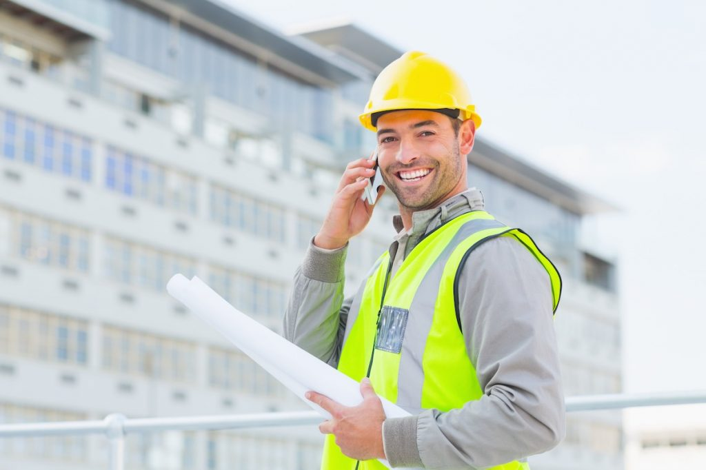 Smiling contractor talking to receptionist via contractor answering service