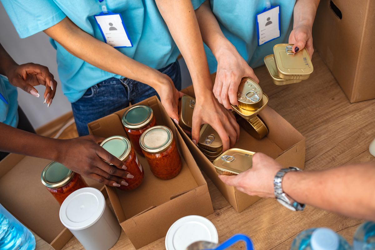 hands filling carboard boxes with donations for employee volunteer program