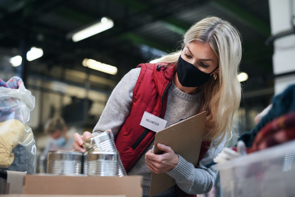 Woman checking food boxes in food bank for employee volunteer program