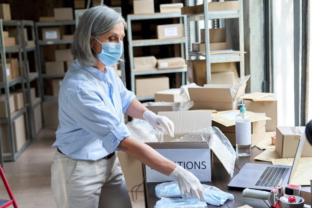 Woman packing food boxes as part of employee volunteer program