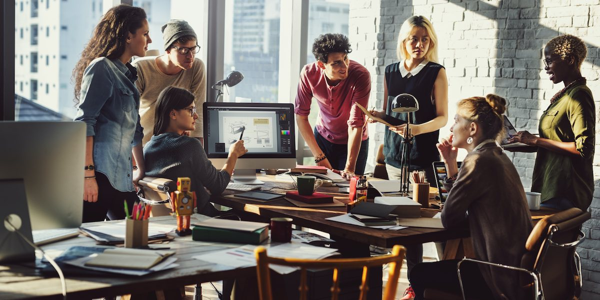 Marketing team stood around desk coming up with campaign concept