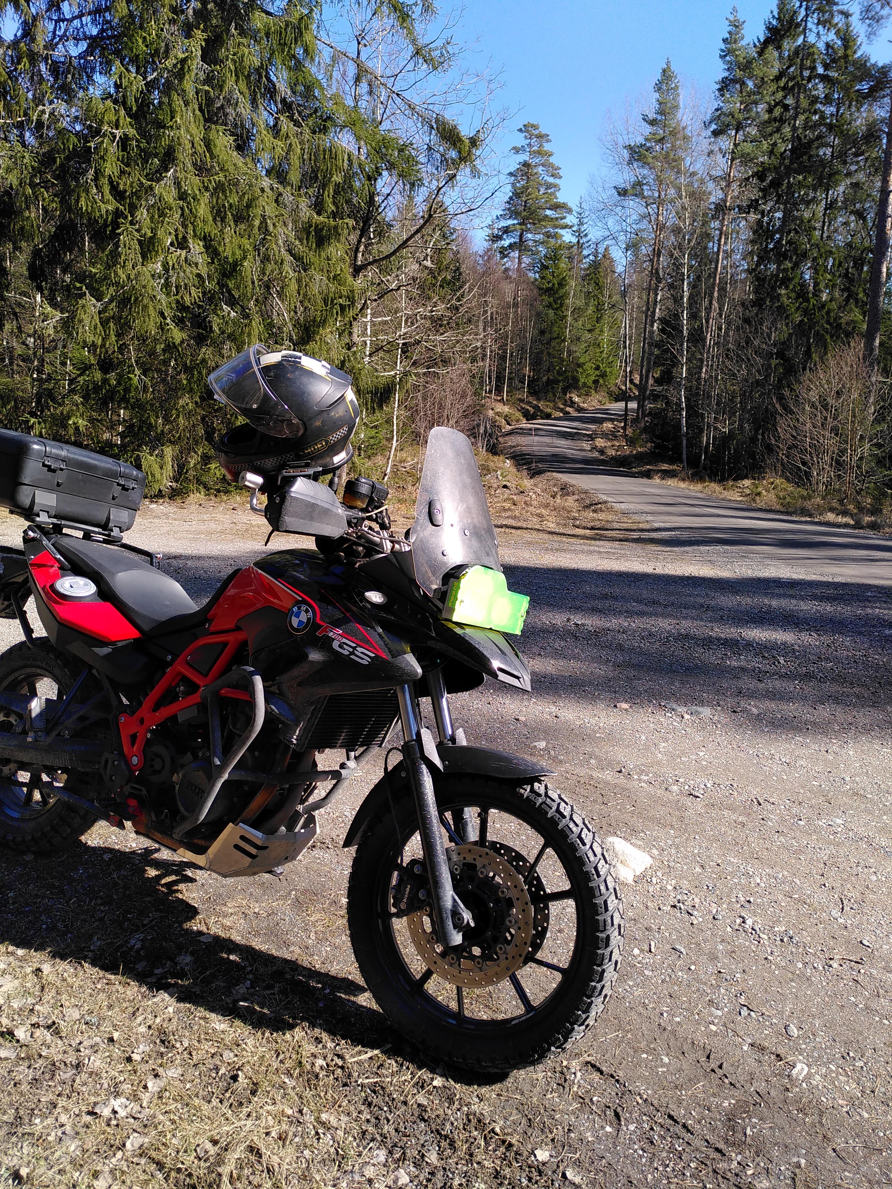 Motorcykel i skogen vid grusväg