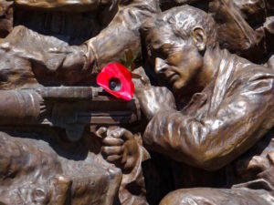 A sculpted poppy is used in lieu of real flowers for this war memorial