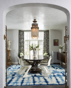 An eclectic dining room uses a tie dye rug to focus the design