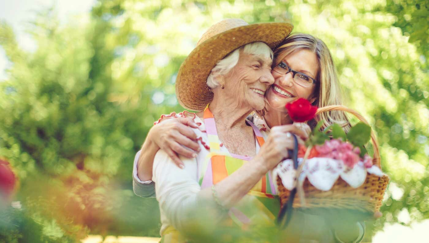 elderly woman picking flowers with her daughter