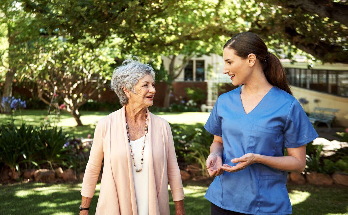 Senior woman walking with a nurse