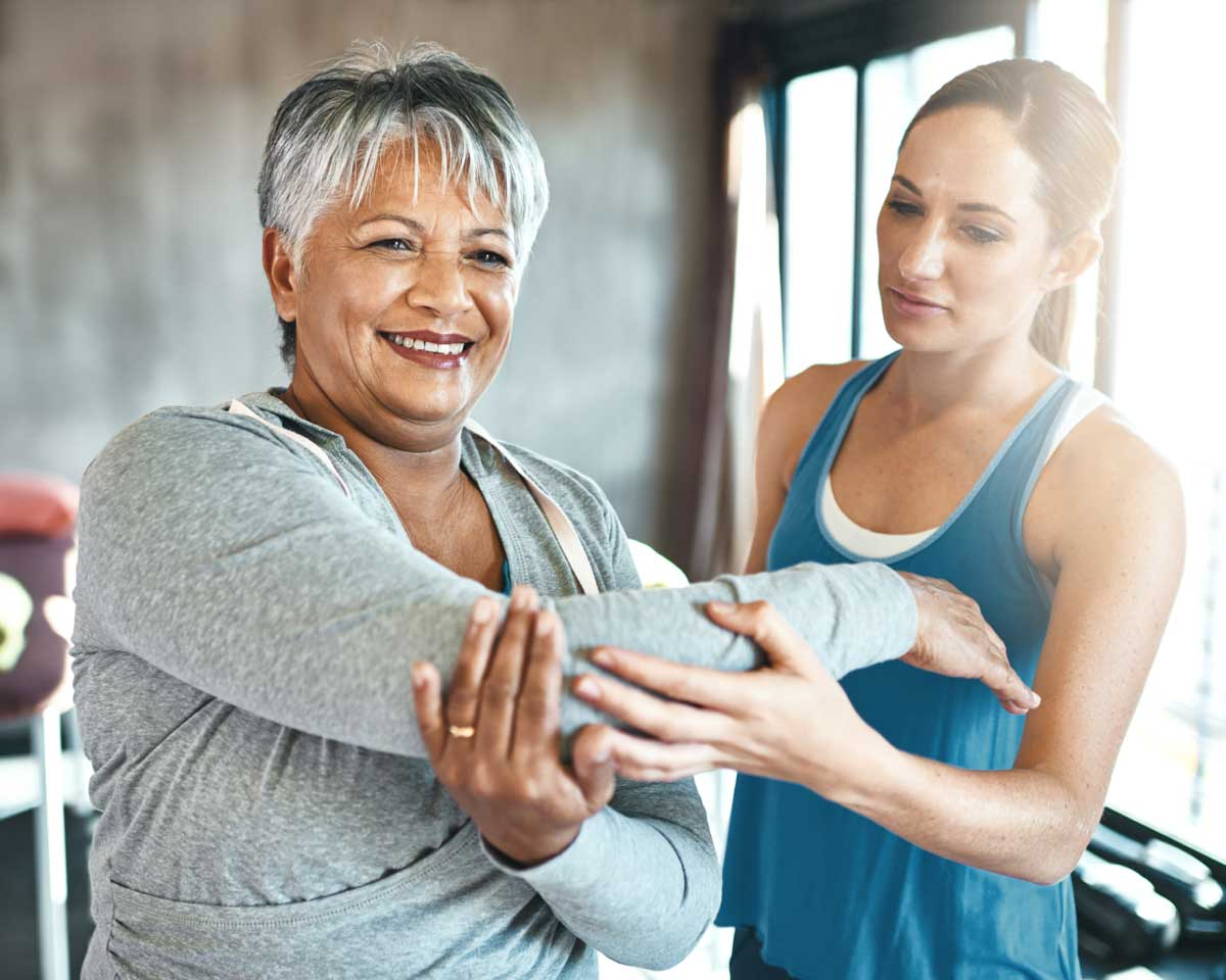 fitness instructor helping a senior woman stretch before exercising