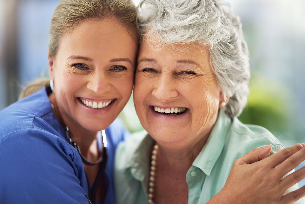 Senior woman hugging and smiling with nurse