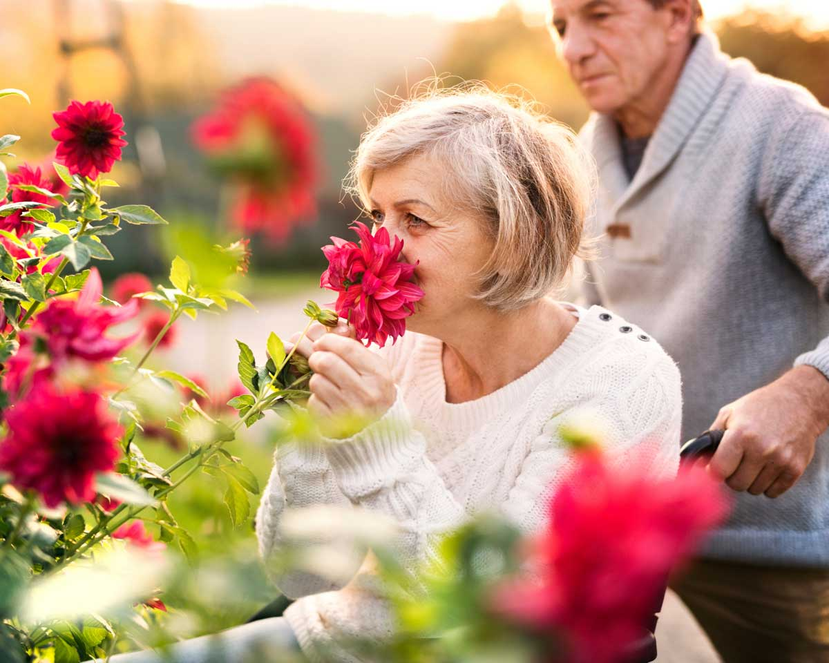 senior couple stops to smell bright red flowers outside their retirement home