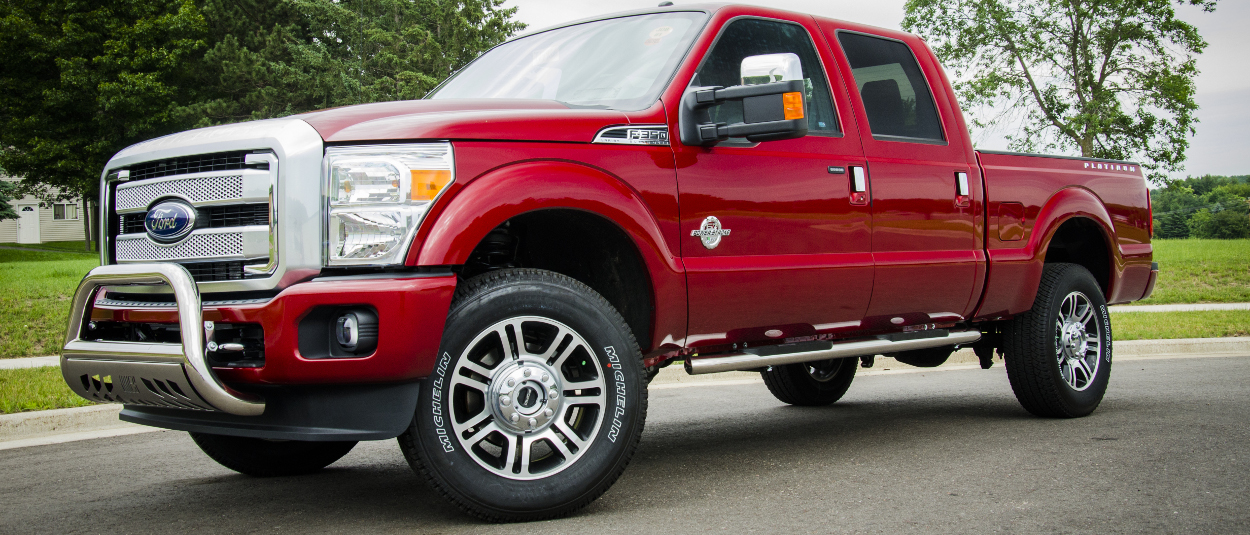 Red 2016 Ford F350 Super Duty with ARIES 4-inch oval side bars and bull bar
