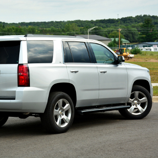 2015 Chevrolet Tahoe with ARIES black step bars - 6-inch oval