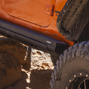 ARIES ActionTrac™ powered running boards on an orange offroad Jeep Wrangler
