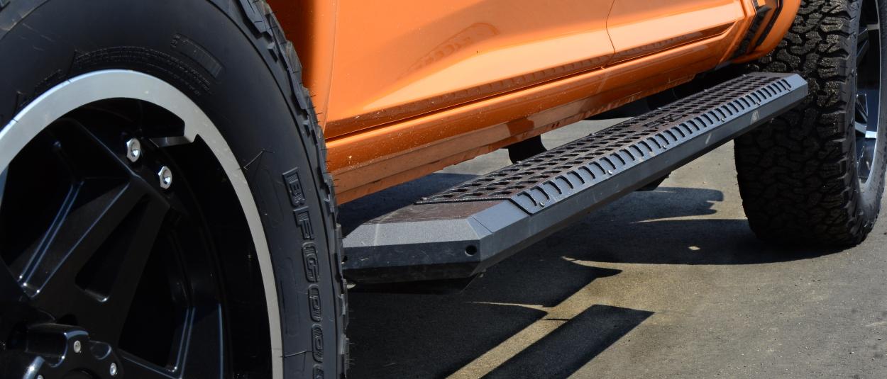 ARIES AdvantEDGE™ running boards on custom build orange truck