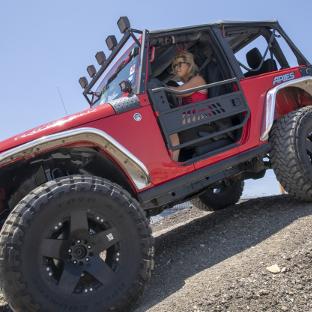 Red offroad Jeep Wrangler JK two-door with aluminum tube doors