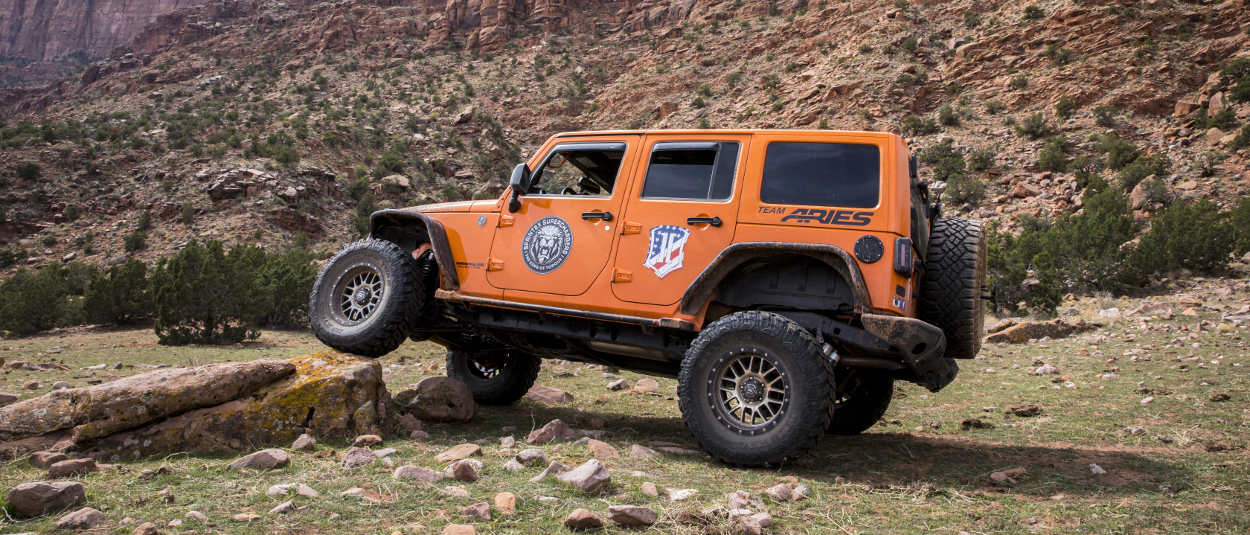 Orange 2013 Jeep Wrangler JK Unlimited rock crawler with ARIES Rocker Steps