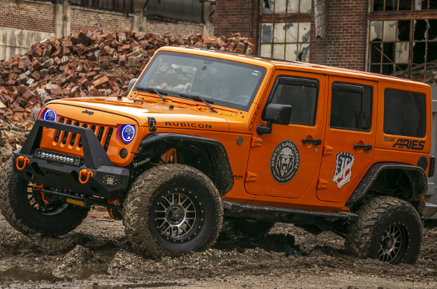 Orange custom 2013 Jeep Wrangler JK Unlimited with ARIES Rocker Steps and Jeep accessories