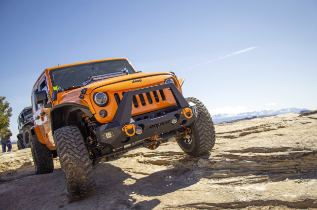 Orange 2013 Jeep Wrangler JK Unlimited rock crawler with ARIES TrailChaser® bumper