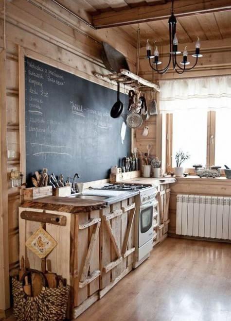 Grande lavagna con scritte in una cucina completamente in legno grezzo naturale