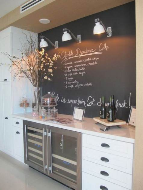 Lvagna con scritte e faretti sopra il top in marmo beige della cucina