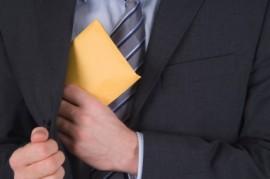 Korruption: Briefumschlag mit Geld wird eingesteckt