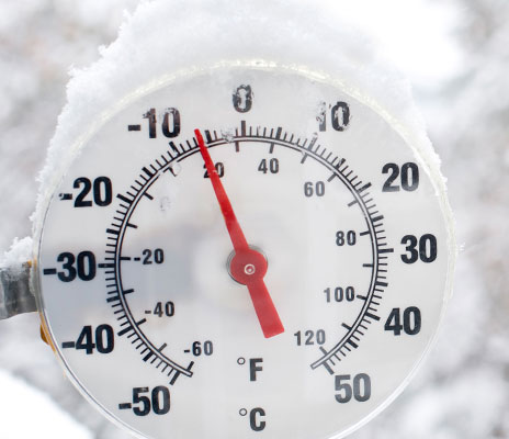 An outdoor thermometer with snow on it