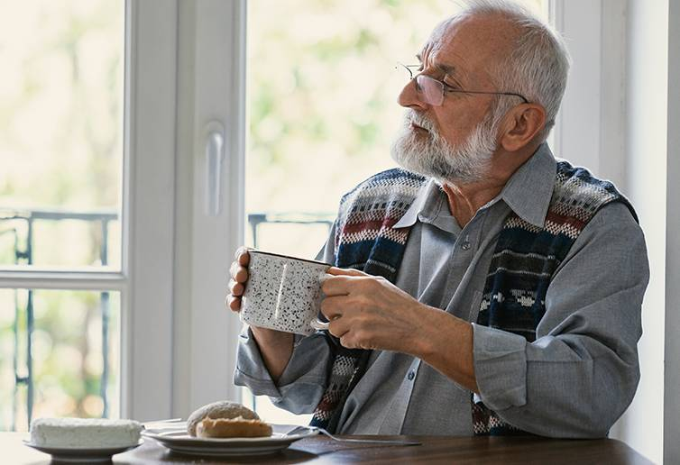 a senior man holding a cup of coffee