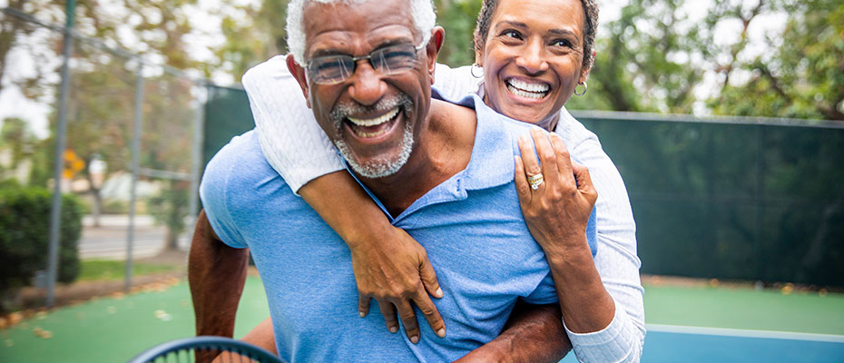 Elderly couple hugging and laughing on a tennis court