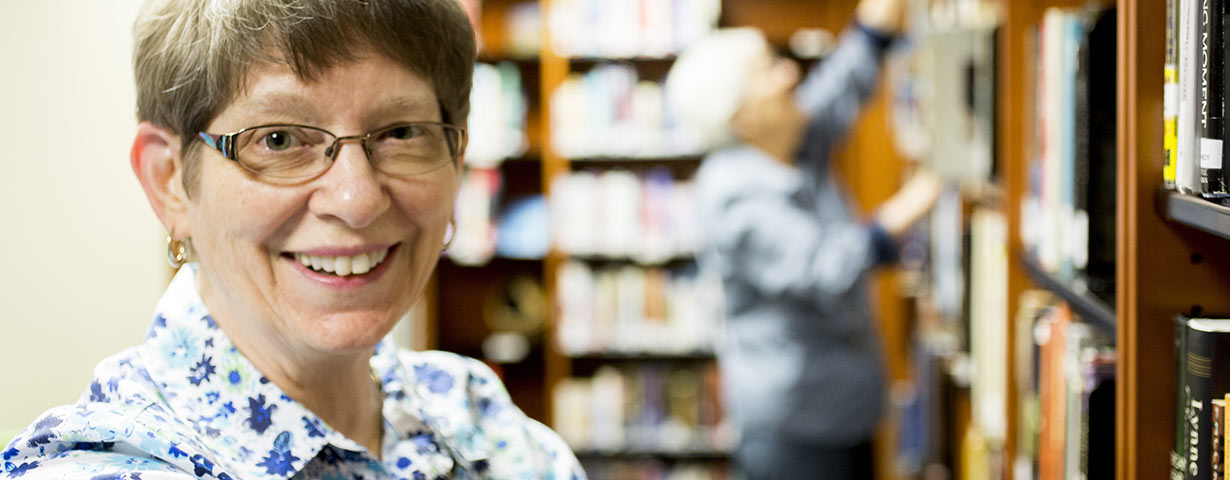 elderly woman with glasses smiling in library a man in background reaches for book