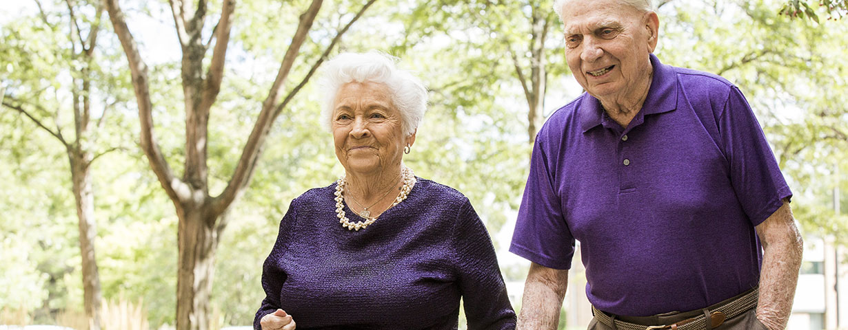 elderly couple in purple planning for senior living community and walking outside