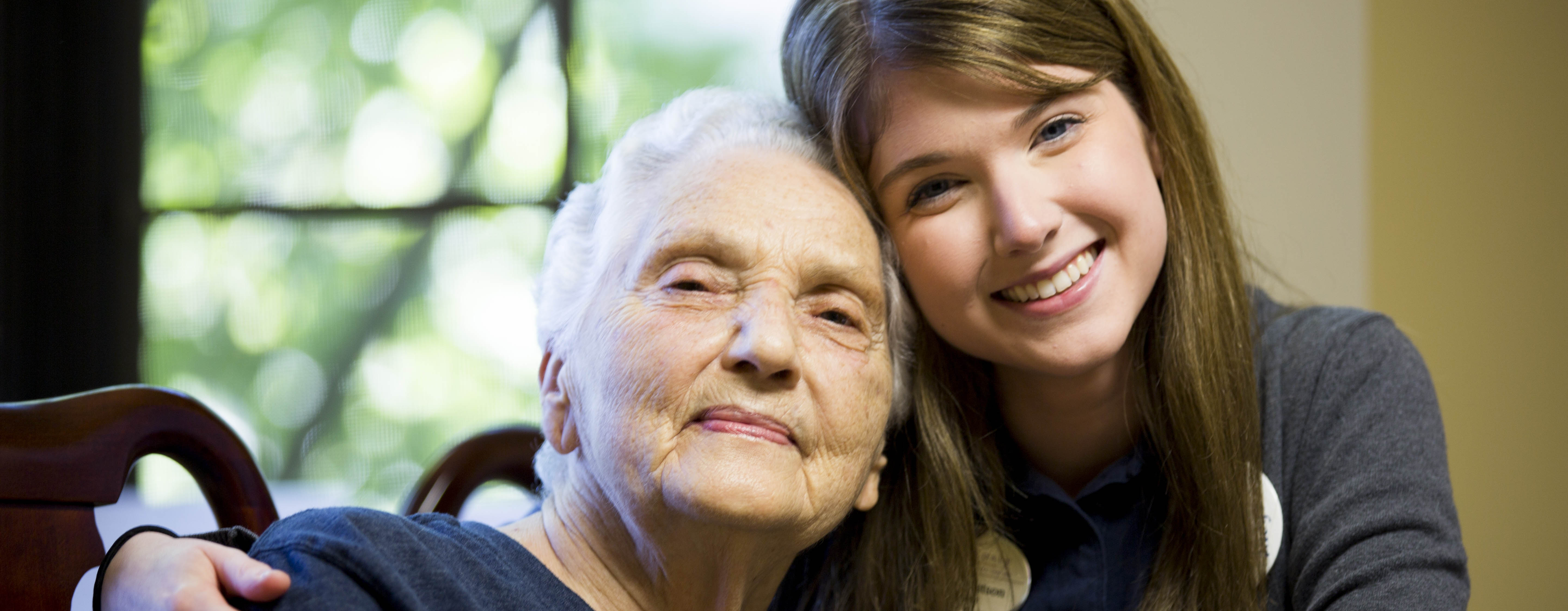 grand daughter and elderly grandmother hugging and smiling