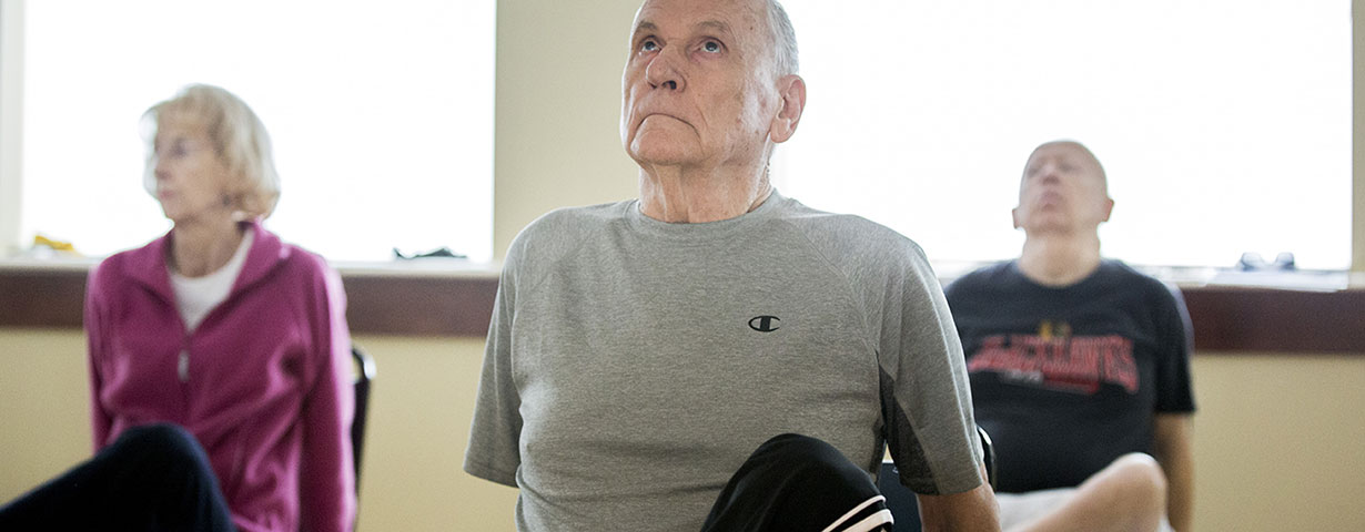 elderly man in athletic clothes working out in room with class of other elderly