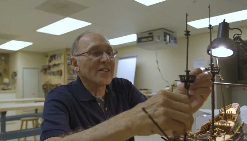 elderly man in workshop constructing wooden miniature ship under light from lamp