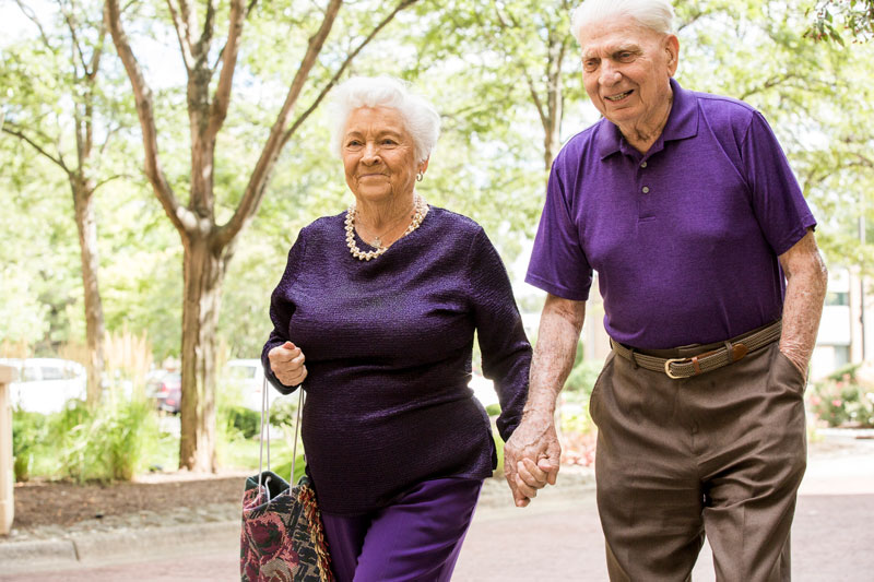 elderly couple in purple holding hands and walking together outside smiling